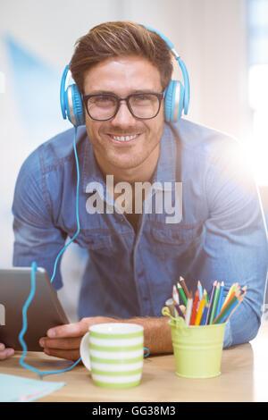 Business executive ascolto di musica digitale compressa Foto Stock