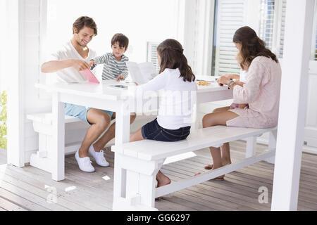 Felice famiglia giovane seduti insieme a casa Foto Stock