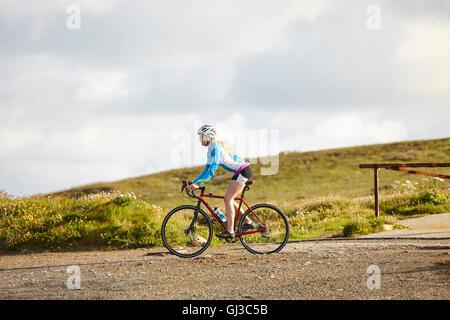 Ciclista equitazione sulla strada di ghiaia Foto Stock