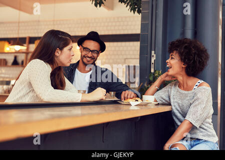 Ritratto di un giovane gruppo di amici a parlare in un bar. Giovane uomo e donna seduta al tavolo del bar e parlare. Foto Stock