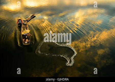 Due pescatori di una rete di colata nel fiume di sunrise, Thailandia Foto Stock