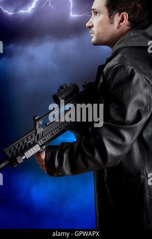 Uomo con lunga giacca di pelle e il fucile di assalto su storm backgr Foto Stock