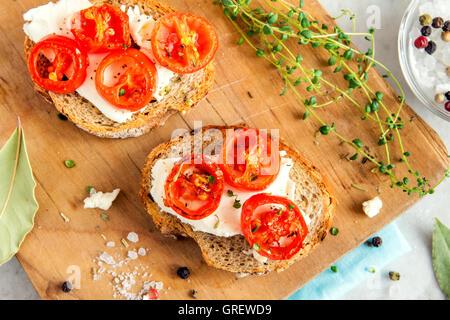 Deliziose bruschette con pomodori arrosto, il formaggio feta e erbe sul pannello di legno Foto Stock