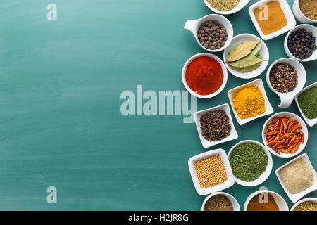 Varie le erbe aromatiche essiccate e le spezie nella ciotola sulla lavagna verde. Foto Stock