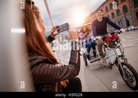 Femmina di scattare fotografie di amici su triciclo ride. Amici godendo le vacanze. Foto Stock