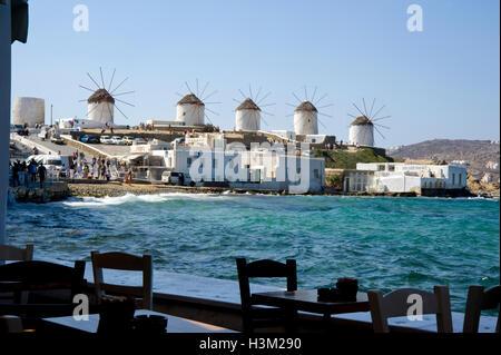 Vista di mulini a vento da seaside cafe a Mykonos Foto Stock