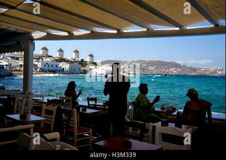 Vista di mulini a vento da seaside cafe a Mykonos, Grecia Foto Stock