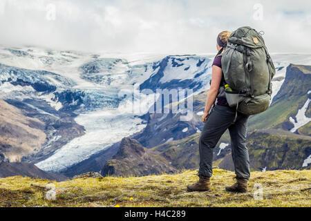 Un giovane escursionista che si affaccia su un ghiacciaio in Thorsmörk Foto Stock