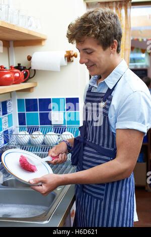 Ragazzo adolescente con lavoro part-time lavaggio fino in Coffee Shop Foto Stock