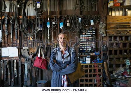 Ritratto fiducioso meccanico femmina con blocco per appunti in officina Foto Stock