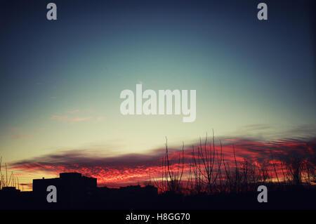 Rosso tramonto Cielo sagome di edifici Foto Stock