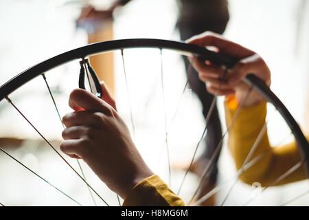 Mechanic esame di una ruota di bicicletta Foto Stock