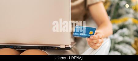 Primo piano su carta di credito in mano di donna con notebook in seduta anteriore albero di natale Foto Stock