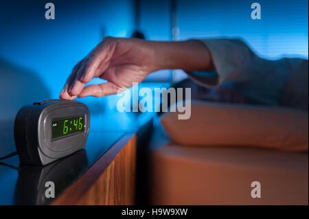 Donna premendo il tasto Snooze di prima mattina sveglia digitale Foto Stock