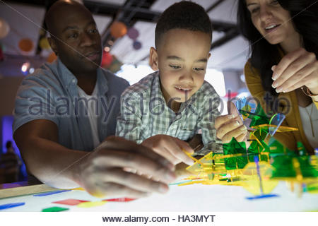 Famiglia giocando con le forme al display luminoso in science center Foto Stock