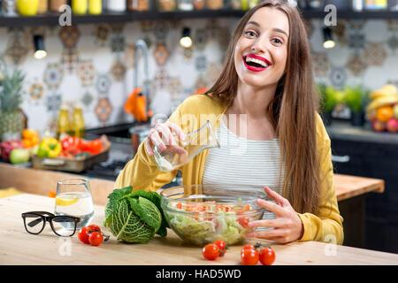 Donna con insalata in cucina Foto Stock