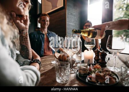 Man mano versando il vino bianco dalla bottiglia in bicchieri con gli amici seduti attorno al tavolo. Un gruppo Foto Stock