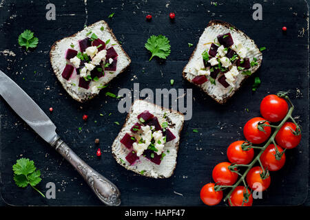 Formaggio di capra, barbabietole tostate e formaggio feta antipasto panini su nero tagliere, vista dall'alto Foto Stock