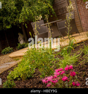 Circular decking area con tavolo e sedie nel giardino inglese Foto Stock