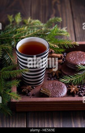 Tazza di tè nero con biscotti al cioccolato e spezie in una scatola di legno Foto Stock