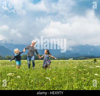 Nonna e nipoti in esecuzione nel campo tenendo le mani, Fuessen, Baviera, Germania Foto Stock