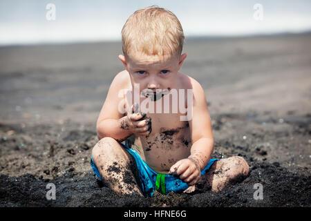 Funny happy baby boy con corpo sporco e la faccia di Sly playing game, mangiando sabbia nera. Viaggio di famiglia Foto Stock