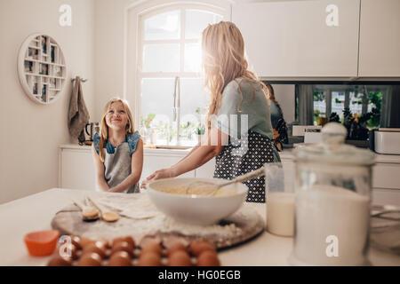 Felice bambina in piedi in cucina e sua madre per la cottura di alimenti. Madre e figlia felice la cottura in cucina. Foto Stock