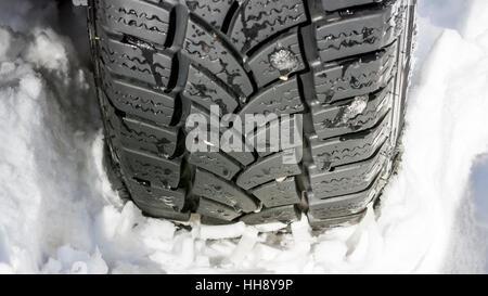 Pneumatico auto sulla strada innevata Close Up. In inverno le condizioni di guida. Foto Stock