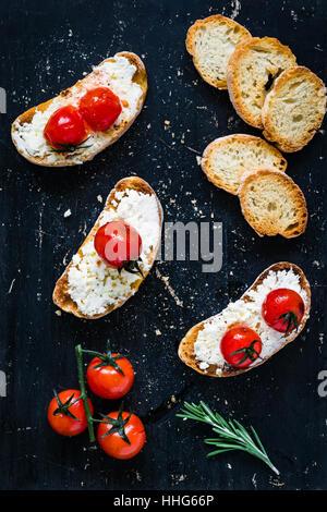 Tostare i crostini bruschetta con bianco fresco formaggio ricotta, arrosto di pomodorini e aglio in olio d'oliva. Foto Stock