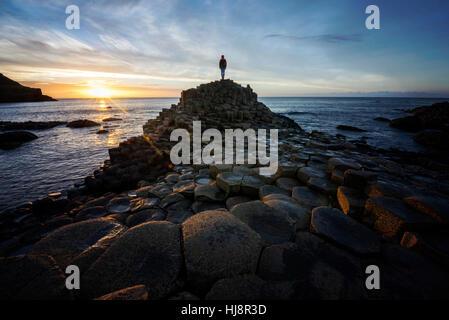 Donna in piedi su Giants Causeway al tramonto, County Antrim, Irlanda del Nord, Regno Unito Foto Stock