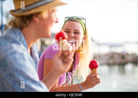 Coppia giovane a ridere e mangiare i coni gelato sul Lungomare, Maiorca, SPAGNA Foto Stock