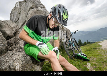 Giovane uomo con gamba ferita seduto sulla roccia con la bicicletta, Baviera, Germania Foto Stock