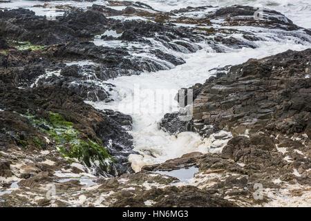 Schiuma di Mare sul roccioso e mossy Oregon Coast in Cape Perpetua Foto Stock