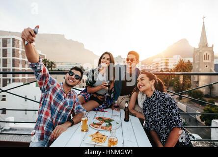 Gruppo di amici avente una parte sul tetto facendo una selfie. Felice giovani prendendo ritratto di auto durante Foto Stock