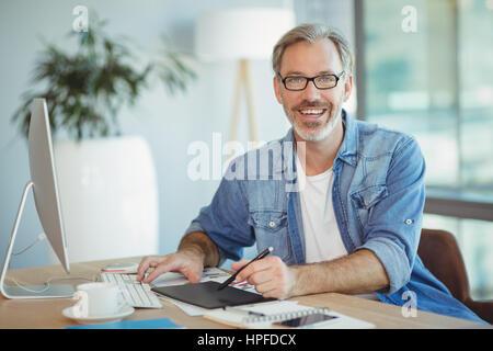 Ritratto maschile di graphic designer con tavoletta grafica in ufficio Foto Stock