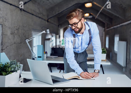 Felice hipster lavora con il laptop dal coworking office Foto Stock