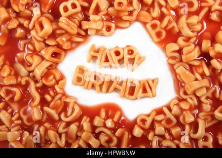 Buon compleanno scritto in spaghetti lettere circondato con lettere illeggibili. Foto Stock