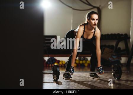 Donna fitness pesi deadlift. Modello di fitness girl il sollevamento pesi in palestra. Foto Stock