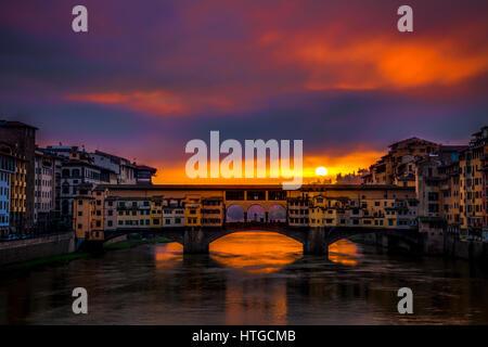 Cancellazione di nuvole temporalesche all'alba crea un drammatico tramonto su Ponte Vecchio a Firenze con il sole Foto Stock