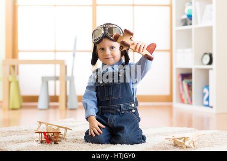 Bambino fingendo di essere aviatore. Kid giocando con gli aeroplani giocattolo a casa Foto Stock