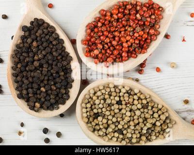Tutto bianco e rosso pepe nero in granelli contro uno sfondo bianco Foto Stock