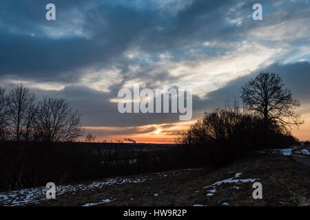 Tramonto sul fiume Daugava con drammatico cielo colorato e sagome ad albero Foto Stock
