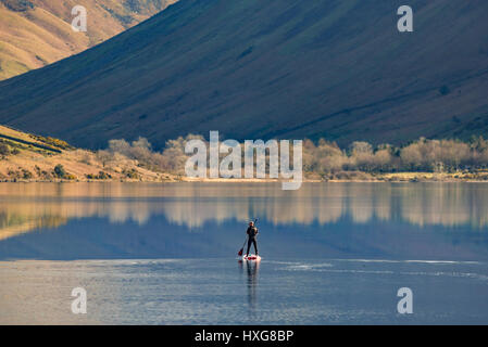 Un lone paddlebaorder sulle acque flatcalm di Wasdale Foto Stock