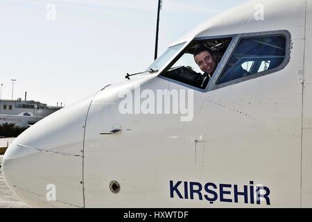 Un sorridente pilota in una cabina di pilotaggio dalla compagnia aerea turca. Foto Stock