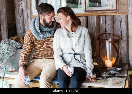 La Svezia, coppia giovane seduto su un tavolo di legno e parlare Foto Stock
