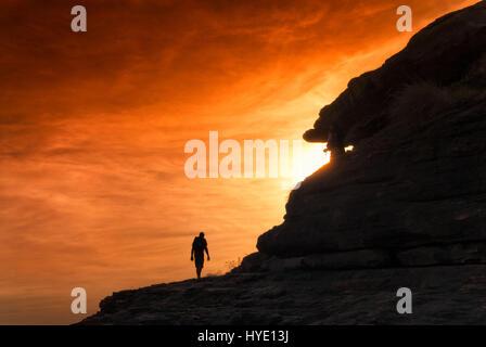 Silhouette di un escursionista salendo verso il tramonto con orange cielo incandescente. Territori del Nord, Australia Foto Stock