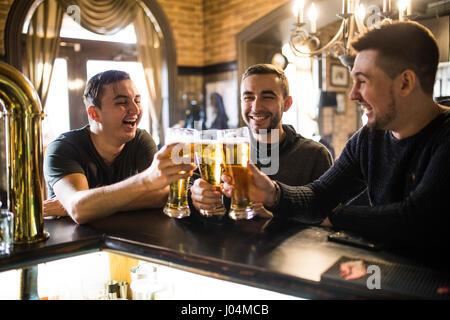 Felice di tre giovani uomini in abbigliamento casual a parlare e a bere birra mentre è seduto al banco bar insieme Foto Stock