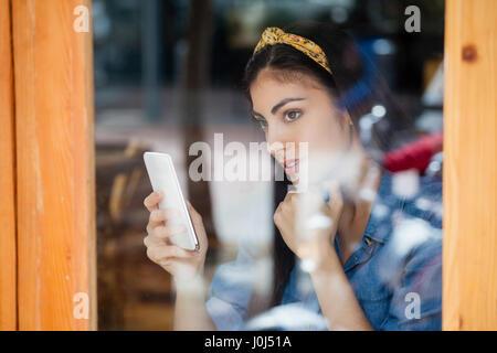 Premurosa donna azienda smart phone mentre è seduto presso il cafe shop Foto Stock