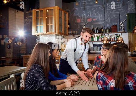 Comunicazione di amici a tavola nel bar cafe Foto Stock