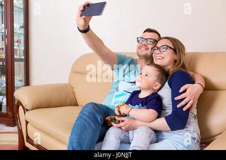 Madre, padre e figlio sorriso, fare selfie sul telefono seduta su Foto Stock